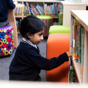Girl choosing a book from bookcase