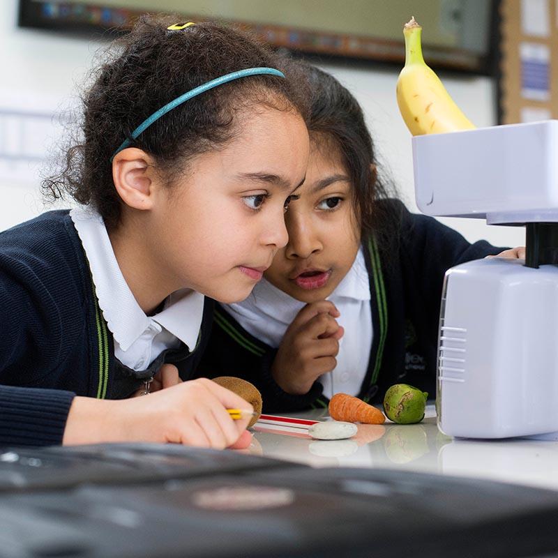 Two girls weighing fruit