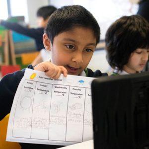Boy holding up written work