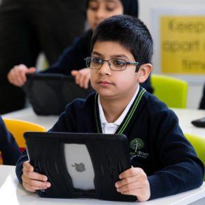 Boy using iPad in class