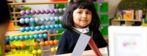 Girl using abacus in maths