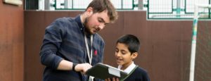 Teacher showing pupils something on iPad