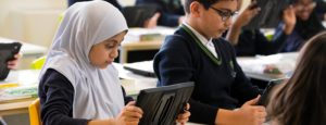 Girl and boy in class using iPads